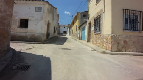 vídeos y material grabado en eventos de stock de pov drive through empty narrow streets with old stone houses against blue sky - villa asentamiento humano