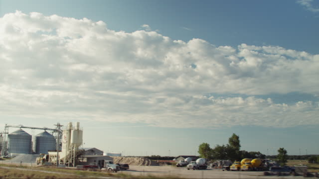 vídeos de stock, filmes e b-roll de drive-by ethanol plant in small rural town and blue sky - etanol
