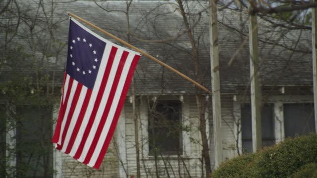 drive-by house in small town displaying us flag with 13 stars. - stars and stripes stock videos & royalty-free footage