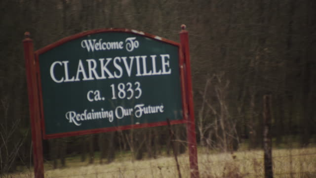 """Drive-by rural roadside sign which reads, """"Welcome to Clarksville - Reclaiming our Future."""""""