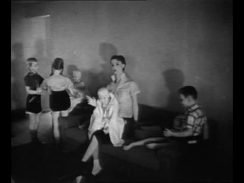drive-by shot model community erected for atomic bomb blast test / group of mannequins, representing mother and children, on a couch in a house... - atomic bomb stock videos & royalty-free footage
