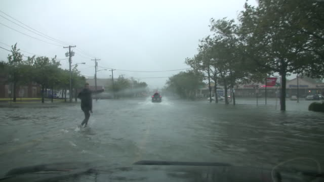 a motorist drives past a pedestrian and through deep flood waters as fast moving storm surge inundates island park ny during hurricane irene's... - storm surge stock videos & royalty-free footage