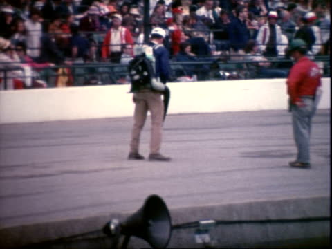 Driver AL UNSER SR talking with pals on track / unidentified race car driver passing sign near spectator stands Please Stay Behind Pit Wall CUs man...