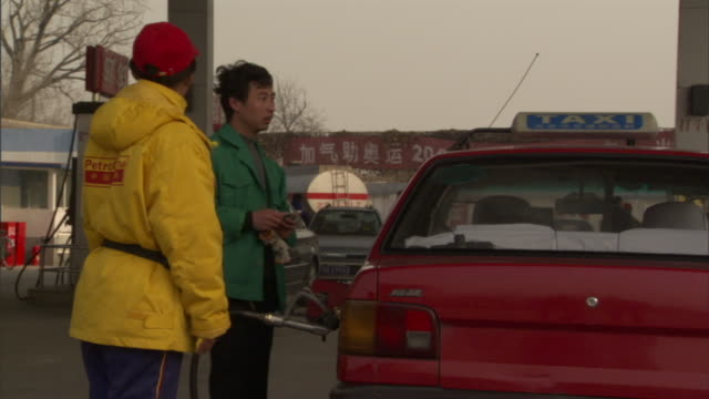 ms driver and female attendant standing next to taxi refueling at lpg filling station, beijing, china - filling station attendant stock videos & royalty-free footage