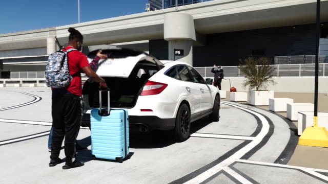 driver and passenger in masks packing luggage and entering car at san francisco international airport, in san francisco, california, u.s., on monday,... - san francisco international airport stock videos & royalty-free footage