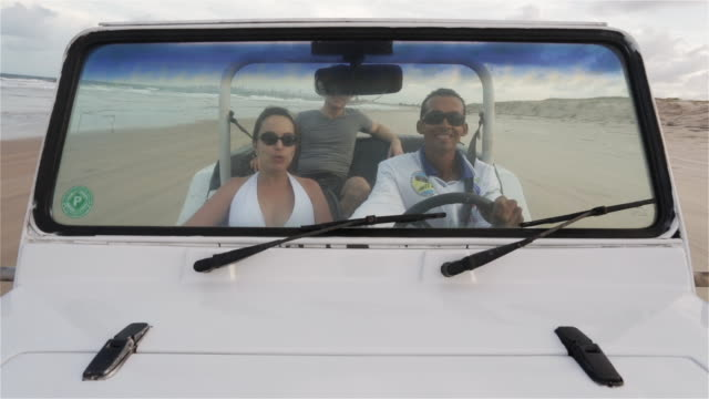 ws, pov driver and passengers in a beach buggy driving along shore / natal, brazil - dune buggy stock videos and b-roll footage