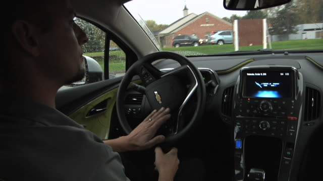 stockvideo's en b-roll-footage met ms pov zo driver behind wheel of electric car / rochester, michigan, united states - hybride voertuig