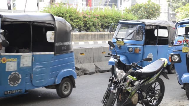A driver boards an auto rickshaw in the Pasar Baroe area in Central Jakarta Indonesia on Sunday May 31 Passengers disembark from an auto rickshaw in...