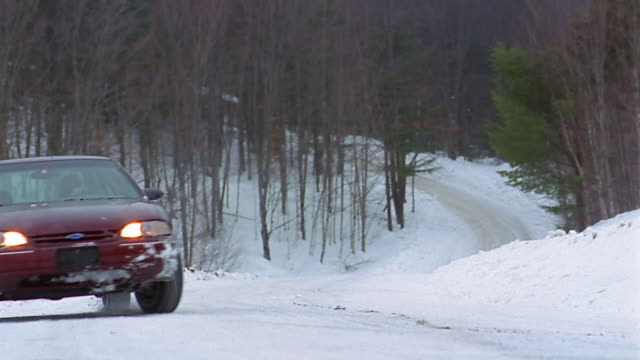 A driver crashes into a snowbank on the side of a country road.