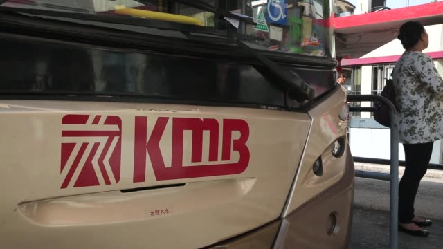 vidéos et rushes de a driver drives a bus away from the kowloon motor bus company limited bus terminal in the tsim sha tsui area of hong kong a bus waits at a kmb bus... - indication de direction