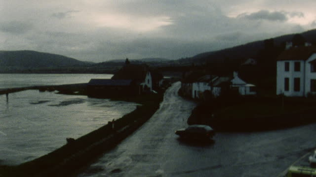 1983 montage driver driving down a road to a building where he parks / porlock, somerset, england - ポーロック点の映像素材/bロール