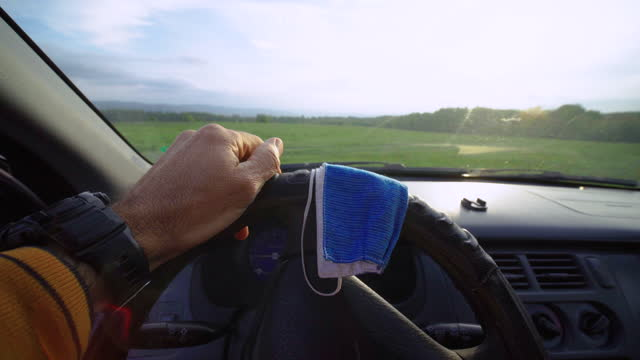 driver pov during covid_19 pandemic. tapping on the steering wheel while waiting for someone or something. putting his protective face mask on the steering wheel. active mature man taking his car to go to work. - day in the life stock videos & royalty-free footage