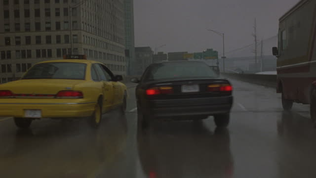 A driver follows behind several cars and swerves back and forth on a highway while it's raining.