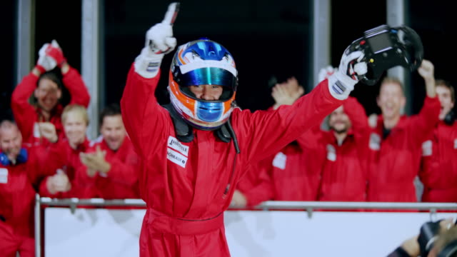 driver getting out of his red formula car and celebrating his victory - crash helmet stock videos & royalty-free footage
