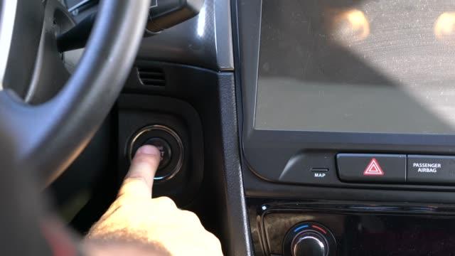 vídeos de stock e filmes b-roll de driver hand pushes engine start stop button. - começo