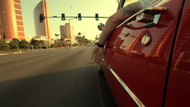 A driver hangs his arm over the door of a red vintage convertible as he travels down Las Vegas Boulevard.