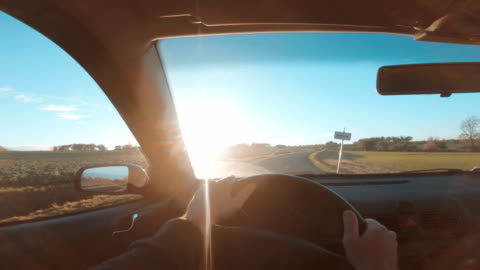 pov of driver holding hands on steering wheel and driving car - car interior stock videos & royalty-free footage