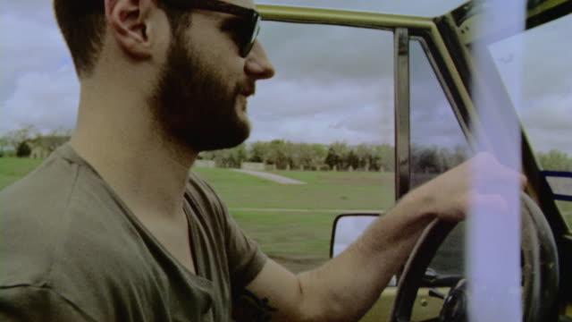 vidéos et rushes de driver laughs and bangs on steering wheel in classic bronco - caméra de cinéma