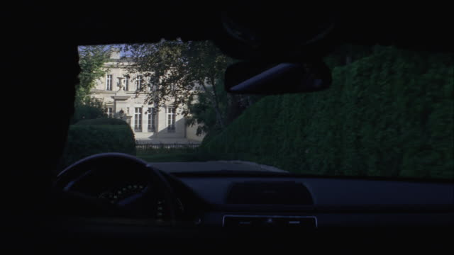 A driver maneuvers a limousine through the grounds of a mansion.