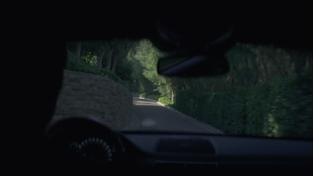 A driver navigates a limousine through the grounds of a mansion.