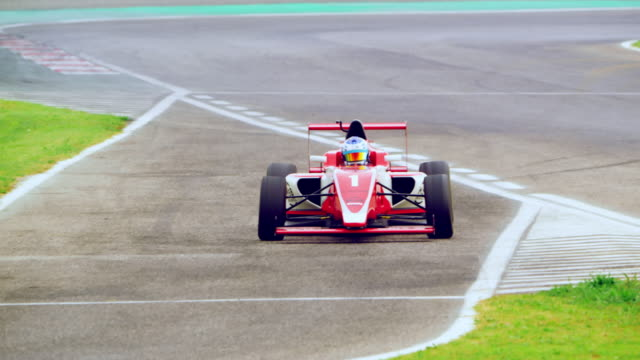 driver of the red formula diverting from the track to make a pit stop - segnaletica stradale video stock e b–roll