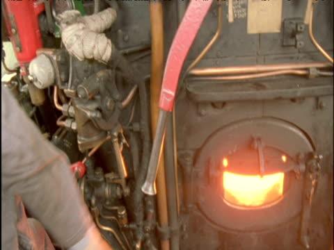 stockvideo's en b-roll-footage met driver pulls regulator lever on steam train scottish highlands - jaar 2000 stijl