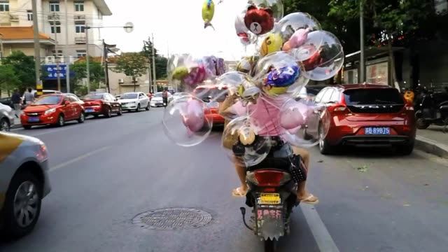 a driver rides an electric bike carrying balloons on the back of a vehicle on june 10 2019 in wuxi jiangsu province of china - small business stock videos & royalty-free footage