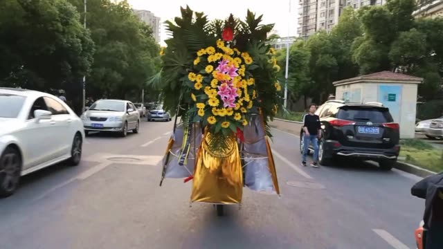 a driver rides an electric bike carrying flowers on the back of a vehicle on april 14 2019 in wuxi jiangsu province of china - wuxi stock videos and b-roll footage