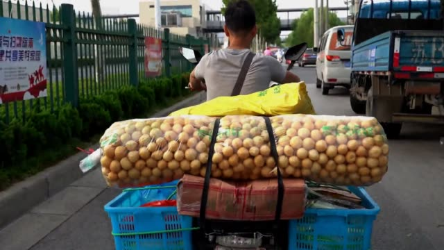 a driver rides an electric bike carrying glutens on the back of a vehicle on august 19 2019 in wuxi jiangsu province of china - wuxi stock videos and b-roll footage