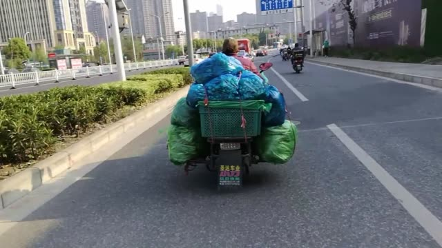a driver rides an electric bike carrying vegetables on the back of a vehicle on april 14 2019 in wuxi jiangsu province of china - wuxi stock videos and b-roll footage