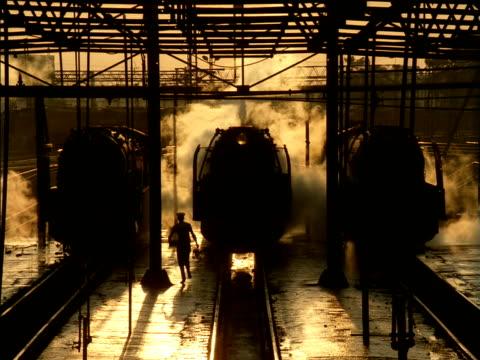 vídeos de stock, filmes e b-roll de driver running towards stationary steam train on platform - imagem tonalizada