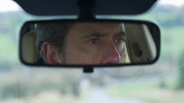 driver seen in rear-view mirror.close-up. - 視界点の映像素材/bロール