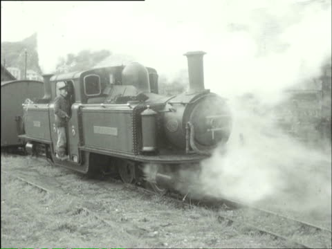 MS Driver showing children putting coals in engine and train level crossing / Stapleford, Nottingham, England