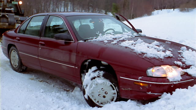a driver steers while a tow truck pulls his car from a snowbank. - tow truck driver stock videos and b-roll footage