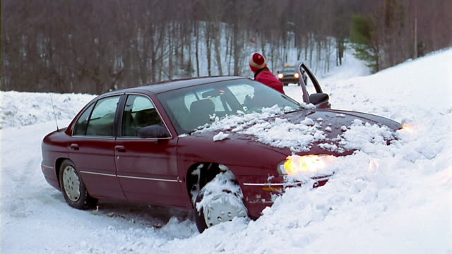 A driver stuck in a snowbank waves down a tow truck.
