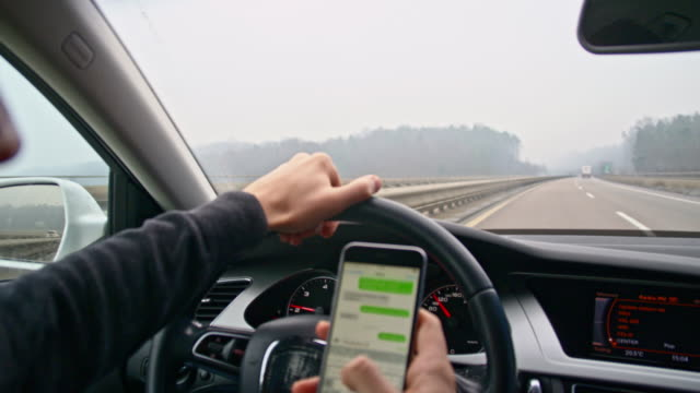 slo mo driver typing sms while driving - distracted stock videos & royalty-free footage