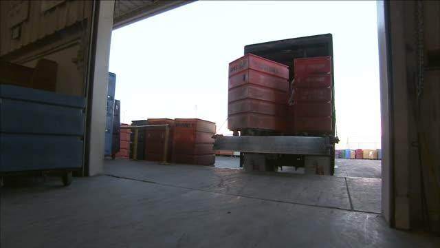 stockvideo's en b-roll-footage met a driver uses a lift gate to unload bins at a receiving dock. - bestelwagen