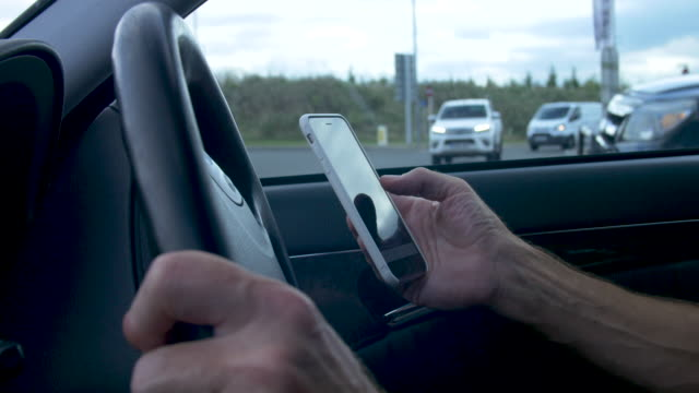 driver using mobile phone while in control of car - dashboard vehicle part stock videos & royalty-free footage