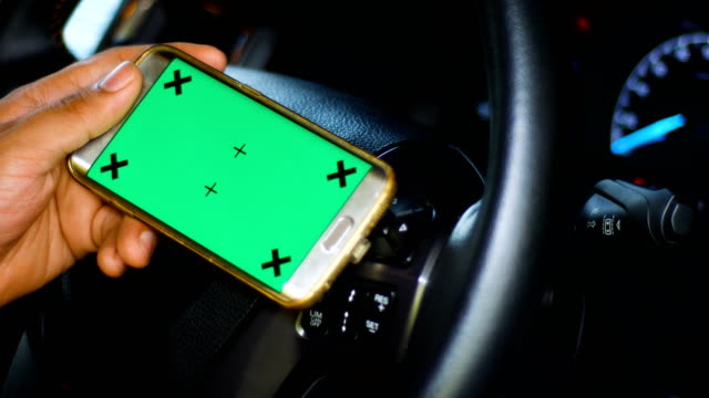 driver using smart phone with green screen in a car, chroma key, dolly shot - wap stock videos & royalty-free footage