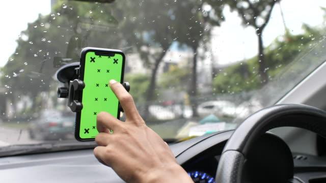 vídeos de stock, filmes e b-roll de excitador que usa o telefone esperto com a tela verde em um carro, chave do chroma - sistema de posicionamento global