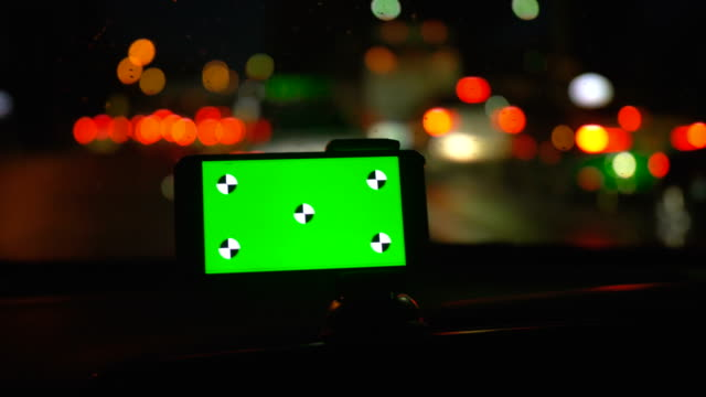 Driver using smart phone with green screen in a car