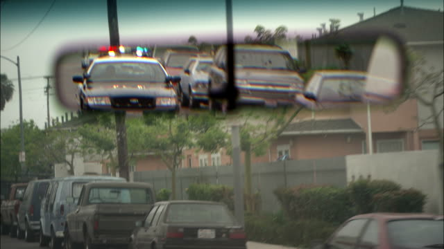 a driver watches the rear view mirror as a police car follows with its flashing lights activated. - quarter stock videos & royalty-free footage