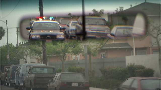 pov  - a driver watches the rear view mirror as a police car follows with its flashing lights activated - pursuit concept stock videos & royalty-free footage