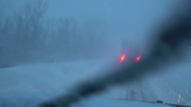 View through the windshield of a car of a semi truck moving slowly as very heavy snow falls on I81 in Upstate New York during an intense lake effect...