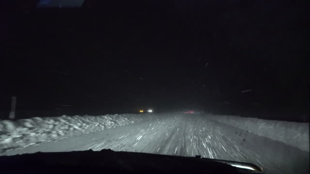 View through the windshield of heavy snow falling on I81 in Upstate New York at night during an intense lake effect snow storm