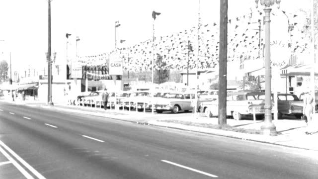 drivers and pedestrians pass a used car lot in 1959. - 1959 stock videos & royalty-free footage