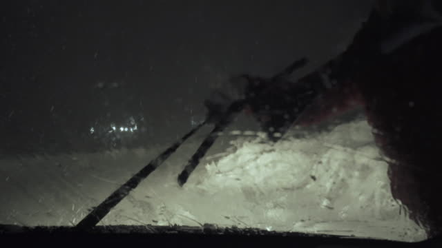 driver's pov driving on snow covered road at night, first snow falling. road illuminated by the headlights and the snowfall. cleaning the windshield wipers from the ice. - extreme weather stock videos & royalty-free footage