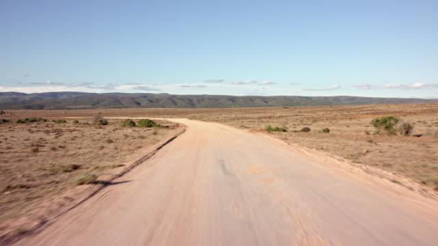 drivers pov - normal pace driving / empty road - part-2: dirt road / dessert - schotterstrecke stock-videos und b-roll-filmmaterial