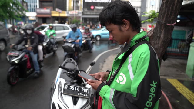 drivers on scooters deliver food and gojek signage on a building in jakarta, indonesia, on tuesday, jan. 5, 2021. indonesia's ride-hailing and... - crash helmet stock videos & royalty-free footage