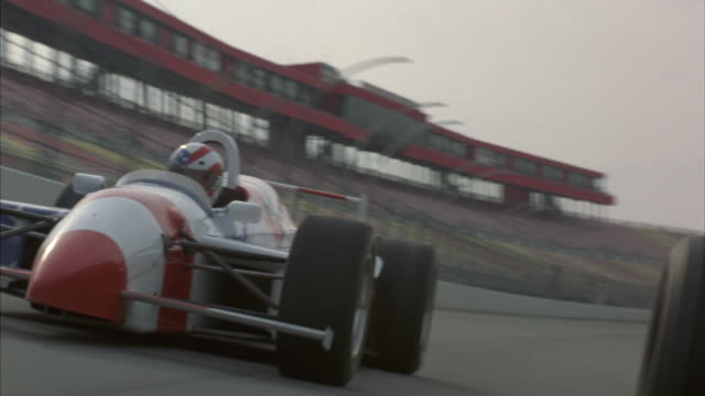 Drivers race their Formula One cars around a speedway.